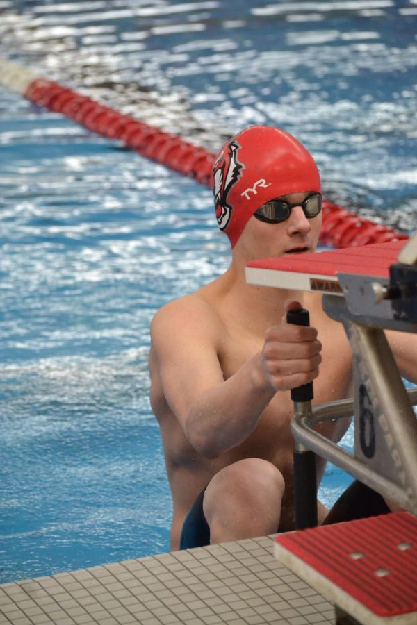 Sophomore Logan Aryes prepares for his start in the 100 backstroke. He placed third in finals. Thinking about how many stroke Im going to take and how many underwaters I will be doing reduces stress and clears your mind, Aryes said.