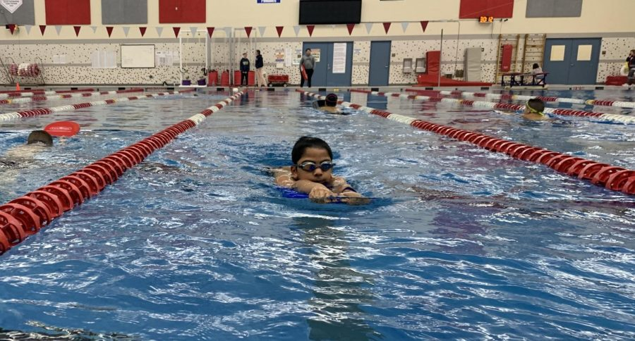 Kids on the Pre-Team use kickboards to warm up at lessons on Feb. 13.