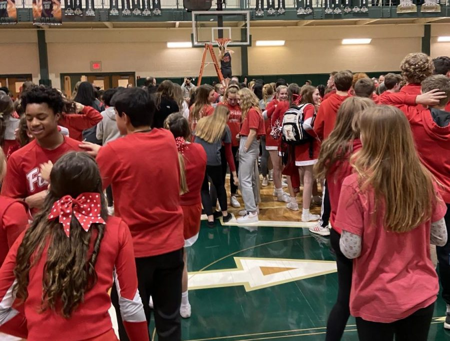 Junior Katie Burton cuts down a peice of the net at Westfield High School after defeating HSE 50-42 to win the sectional 8 championship on Feb. 8.