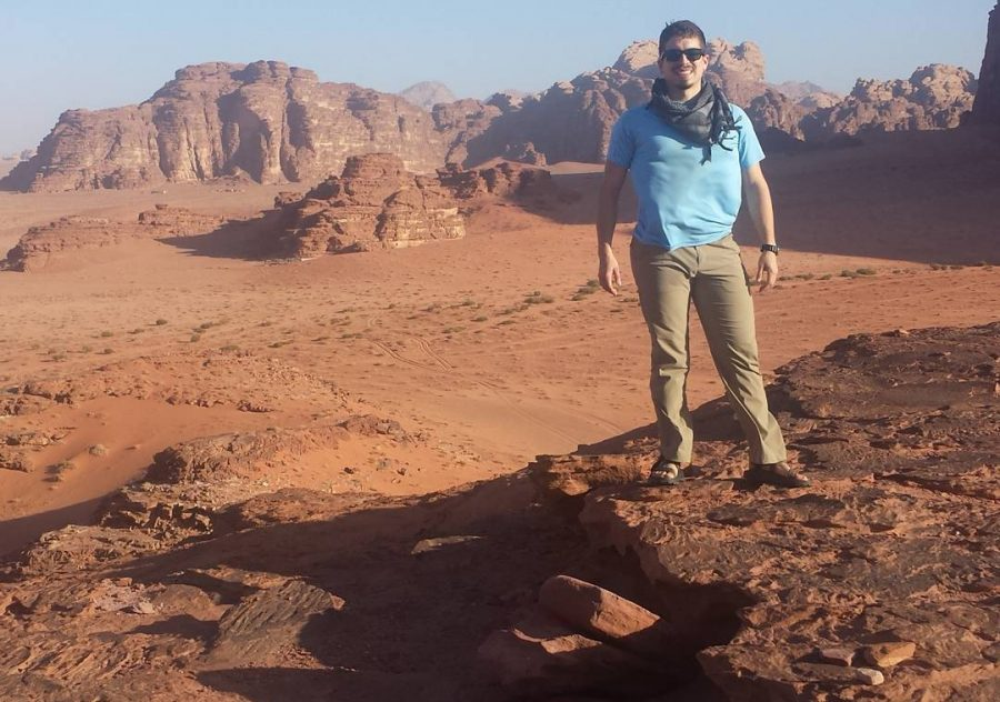 Bernard stands on a rock structure in the desert in Wadi Rum, Jordan on a visit while stationed Bahrain.