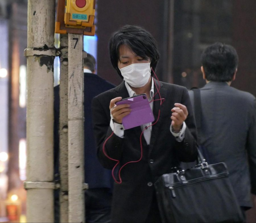 Tokyo man wears a courtesy mask while reading his phone.