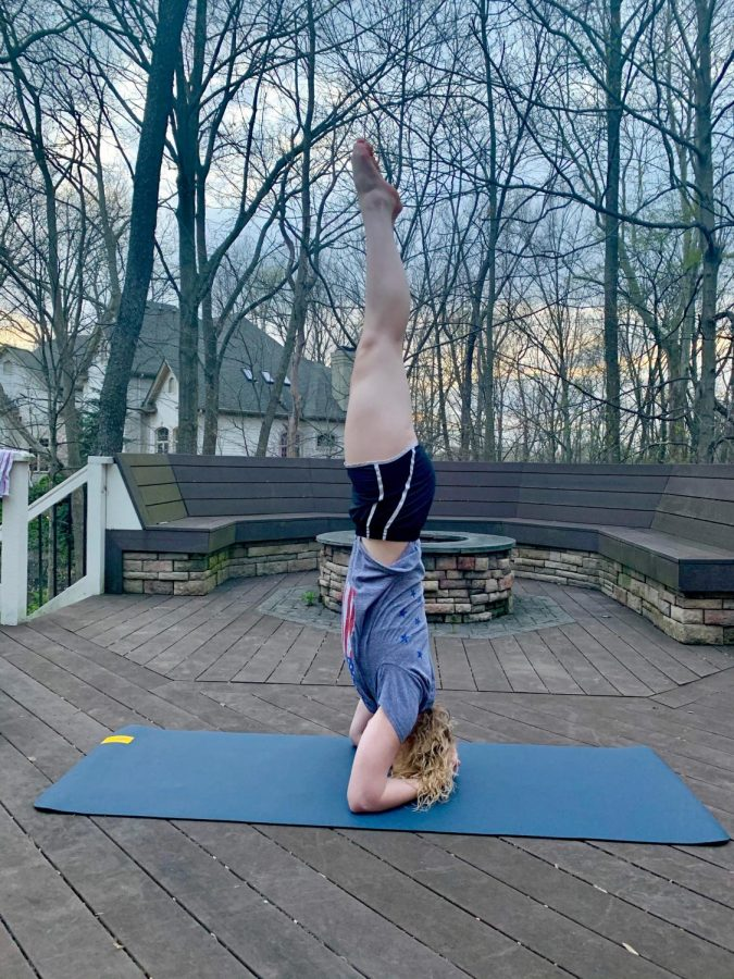 Junior Natalie Bryan does yoga on her back porch to give herself fresh air and a break from working on school work.