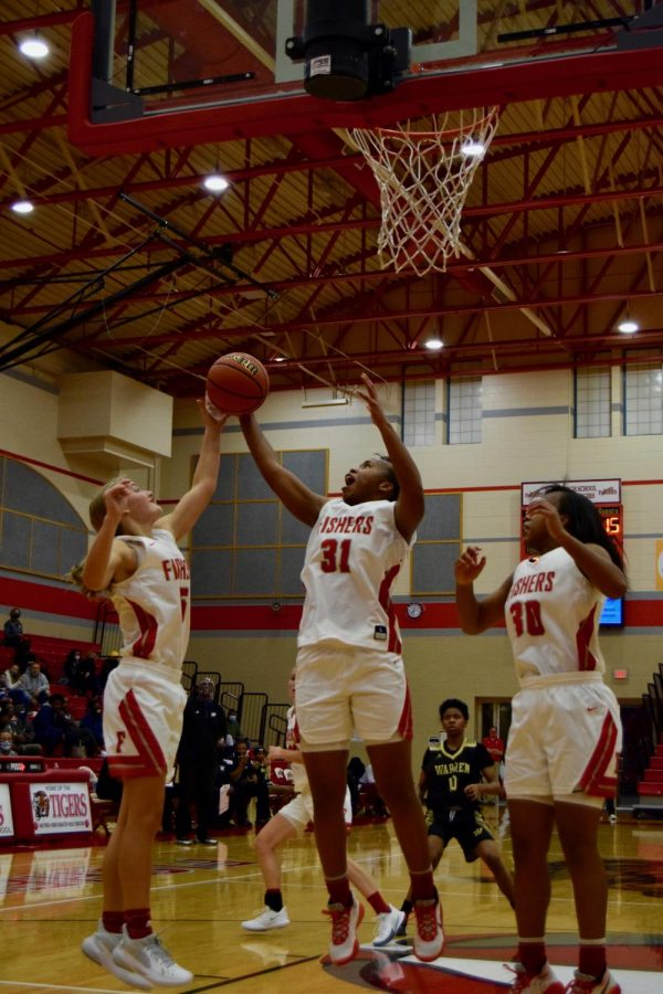 """Senior Audra Emerson and sophomore Olivia Smith both go for the defensive rebound while Smith watches. """"Our team brought back a lot of talent from last year and I think that talent will take us far this year."""" Emerson said. The Lady Tigers defeated Warren Central 56-35 in a home game on Nov. 3. FHS record as of Nov. 5 is 2-0."""