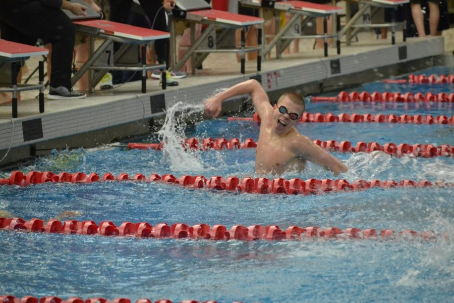 Junior Kyle Ponsler splashes water in celebration after winning the 200 freestyle relay against rival HSE at the sectionals meet on Feb. 22, 2020. Ponsler set new pool and school records for the race at the meet.