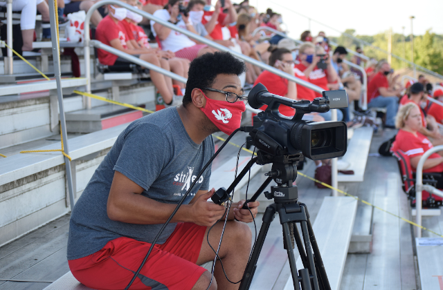 Senior FSN member Jackson Williams points his camera towards the action during a football game against Pike on Aug. 28. Fishers lost 28-24.