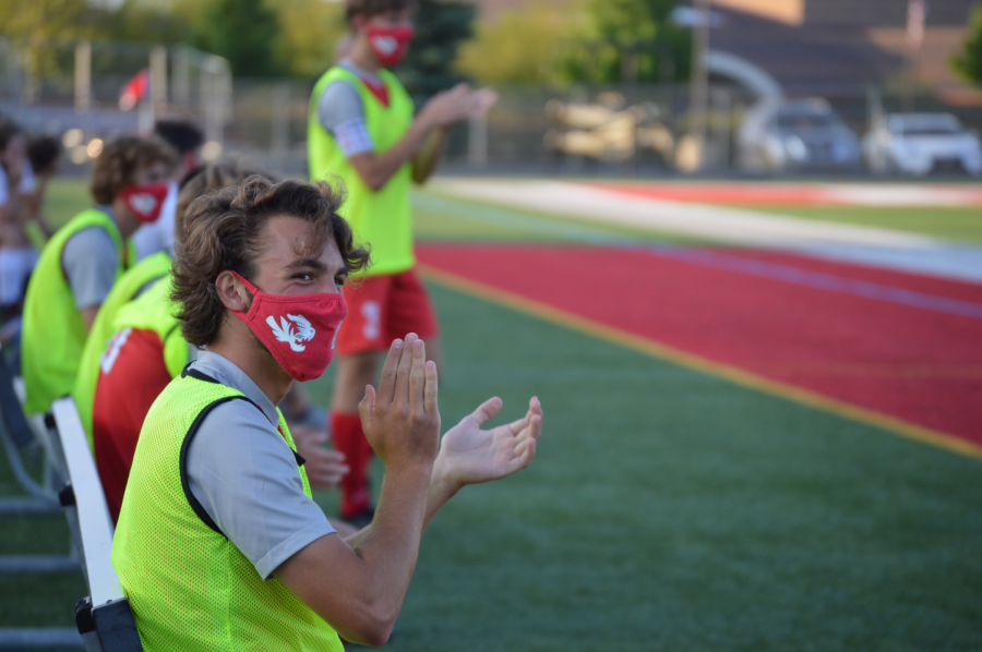 Senior Ryan Elick cheers on his team from the sidelines while wearing his required mask, one of the regulations set by the IHSAA.