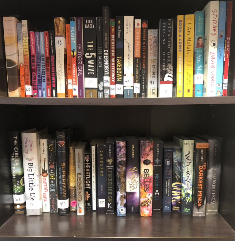 A shelf displays books ranging from classics to young adult novels.