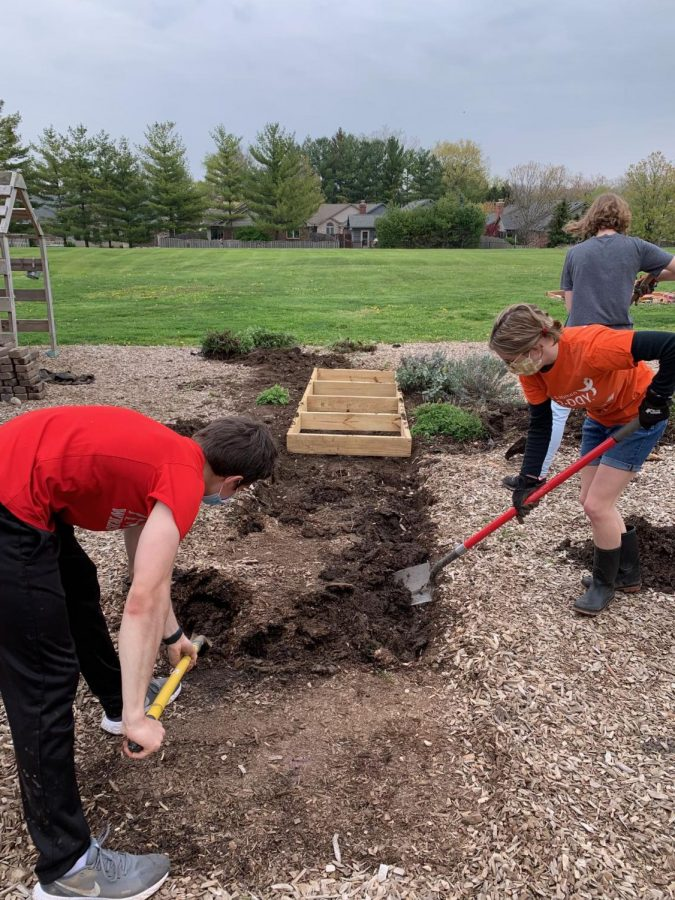 Seniors Dylan Parodi, Izzy Alexander and Mia Driskell work to dig a hole for the new sensory pathway frame. Sensory pathways are known to increase motor skills and a sense of balance and provide an outlet for stress relief.