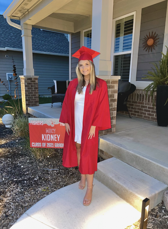 Kidney poses for a photo with her cap and gown next to her sign outside her house on May 10 for the senior video.