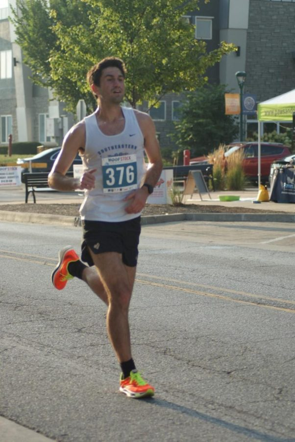 A 5K participant sprints down the pike on Aug. 21 and continues on to the finish line to complete his run in 22 minutes. He was the first participant to finish the 5K, which he received an award for later on during the event.