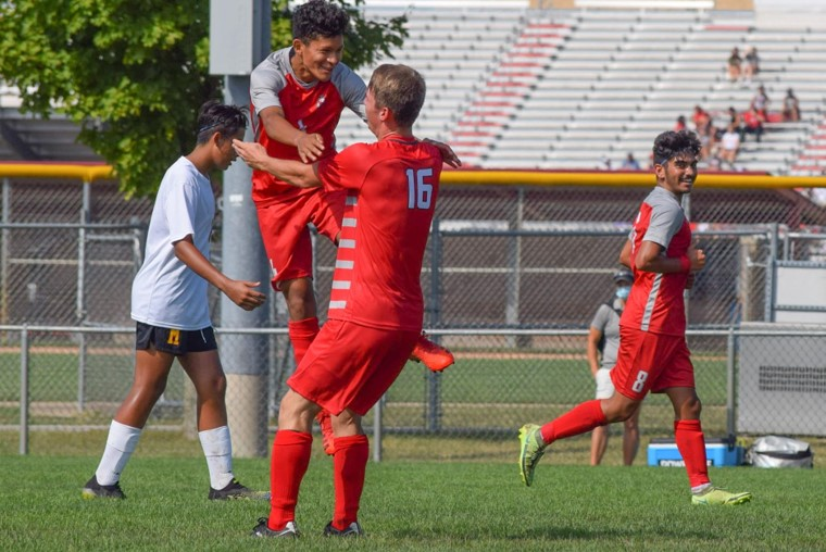 Junior Aywan Ishaq smiles while Sophomores Ashton Slater and Kevin Davalos celebrate after scoring a goal. The JV team defeated McCutcheon 7-0.