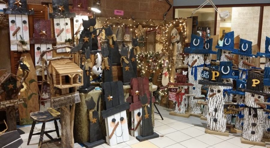 Decorative wooden pieces such as snowmen and cats sit in one of the cafeterias and are available for purchase at a vendor booth during a previous Christmas in October craft fair.